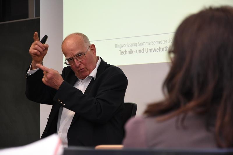 Prof. Uwe Wiemken erklärt wird mit Wort, Schrift und Gestik.