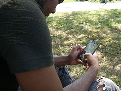 Mann schaut auf sein Smartphone, Blick über die Schulter