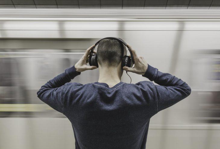 Mensch steht mit Kopfhörern an der U-Bahn Station