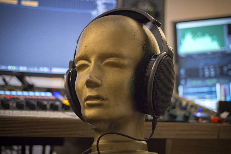 An artificial head with headphones in a studio environment