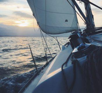 Schiff segelt auf dem Meer in Richtung Sonnenuntergang