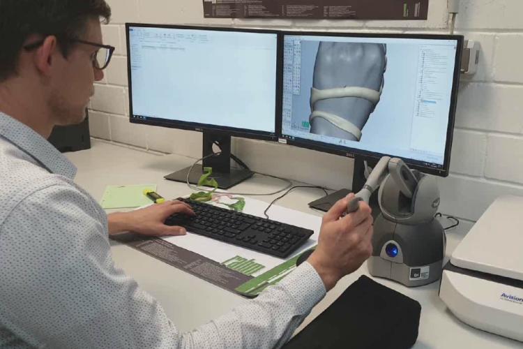 Ein Mann sitzt an einem Schreibtisch. Vor ihm zwei Bildschirme. Mit der rechten Hand hällt er einen Stift, der an einem kleinen Roboterarm hängt. Auf dem Bildschirm ist eine digitale Version der Orthese zu sehen.