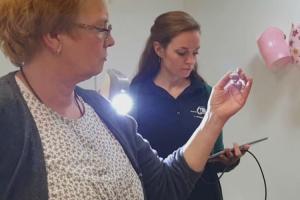 Zwei frauen stehen in einem Raum. Die älter Frau haält ihre Hand vom Körper entfernt während die Andere mit einem Laser diese Hand abscant