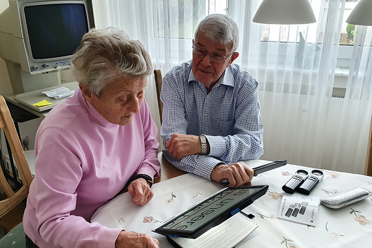 Frau Mack testet die digitalen Lesehilfe, wobei ihr Mann sie unterstützt
