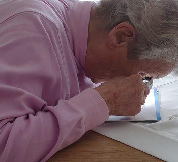 Auf diesem Bild bedient Frau Mack ihre Lupe um einen Text zu lesen. Mit ihrer Lupe muss sie sehr nah an ihren Text heran.