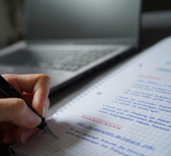 Ein Block, auf dem mit einem Füller handschriftliche Notizen gemacht werden. Links davon ein Notebook.